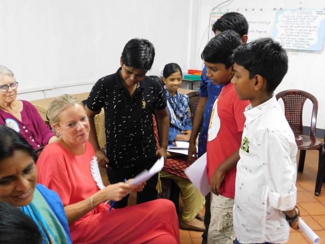 Students crowd around Professor Anne Stillman during her poetry workshop
